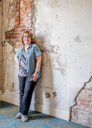 Melody Lapczynski stands in front of a wall on the third floor of the renovated Carlisle Hotel. The Hall is important because of it is remembrance of the fire and what had happened to the building when the rest of the hotel was rehabbed.