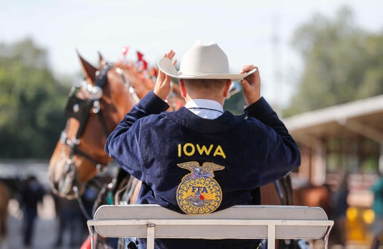 A young FFA member adjusts his hat while waiting to enter the show ring during the Iowa 4-H and FFA livestock show on Friday, Aug. 7, 2020, at the Iowa State Fairgrounds.