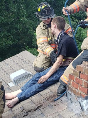 Cody Methanial Sargent is checked out by an Evansville firefighter after being pulled out of a chimney. Sargent was attempting to escape police who had a warrant for his arrest, went up into the chimney and got stuck.