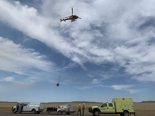 Firefighting helicopter with water bucket working to suppress the Pumpkin Fire burning southwest of Miles City.