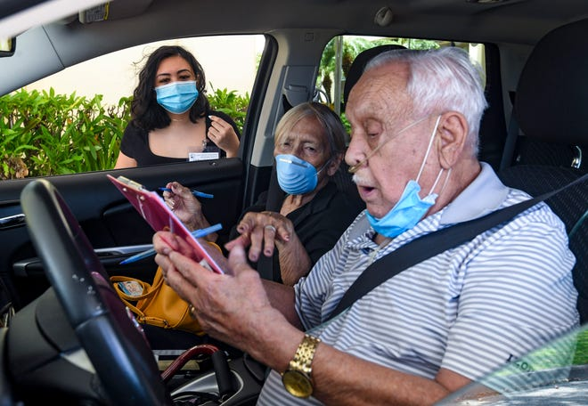 Sinajana couple, Annie and Roy Gogue, are assisted by Guam Election Commission employee, Chellsea Anderson, as they prepare to cast their absentee ballots for the primary election via curbside service, being offered as part of the ongoing in-house voting by the agency, outside the GCIC Building in Hagåtña on Friday, Aug. 7, 2020.