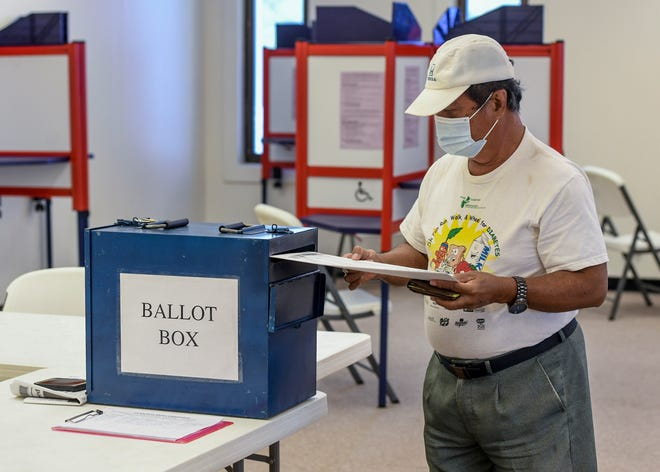 Tamuning resident, Ernesto Wenceslao, inserts his absentee ballots into a ballot box after making his electoral selections for the primary election during ongoing in-house voting at the Guam Election Commission in Hagåtña on Friday, Aug. 7, 2020.