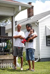 Deontez Boyd, left, poses for a photo with Kerry Boyd, right, while holding his daughter, Kerrysa Boyd, at their home off of South Sherman Drive in Indianapolis, Tuesday, August 4, 2020. Boyd is one of the many people in Indianapolis who are behind on rent due to job layoffs during the coronavirus pandemic.