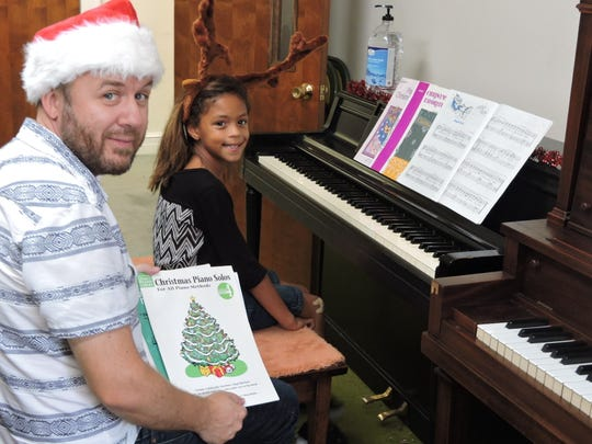 In pre-pandemic days: Ben Maney helps his student Makaia Gray get in a festive mood to practice her piece for the 2016 Community School of the Arts Holiday Concert. Sept. 26, 2016.