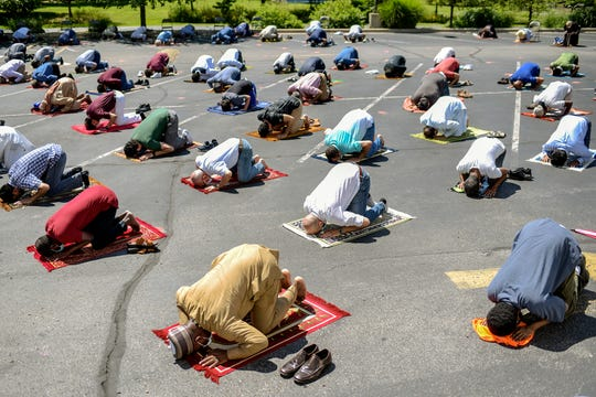 People participate in the first large in-person Friday congregation prayer since COVID-19 restrictions in the parking lot of the Islamic Center of East Lansing on Friday, Aug. 7, 2020.