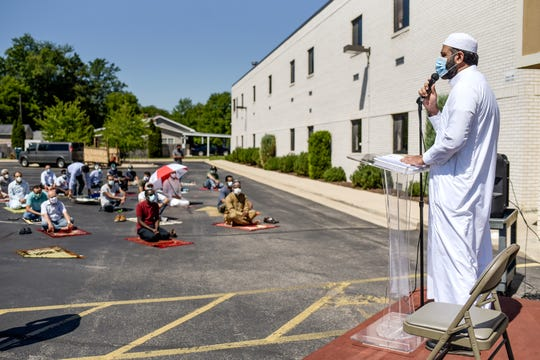 Imam Sohail Chaudhry gives a sermon in the parking lot during the Friday congregation prayer on Friday, Aug. 7, 2020, at the Islamic Center of East Lansing. It was the first large in-person prayer service since the COVID-19 restrictions.