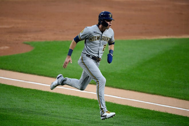 The Brewers' Christian Yelich  rounds the bases in the third inning on his inside-the-park home run.