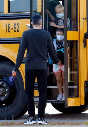 Pearre Creek Elementary School students exit a bus as they are greeted by a faculty member for the first day of school on Aug. 7, 2020, in Franklin, Tenn.