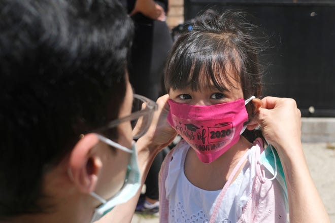 In this June 10, 2020, file photo, Olivia Chan's father helps her with a new mask she received during a graduation ceremony for her Pre-K class in front of Bradford School in Jersey City, N.J.