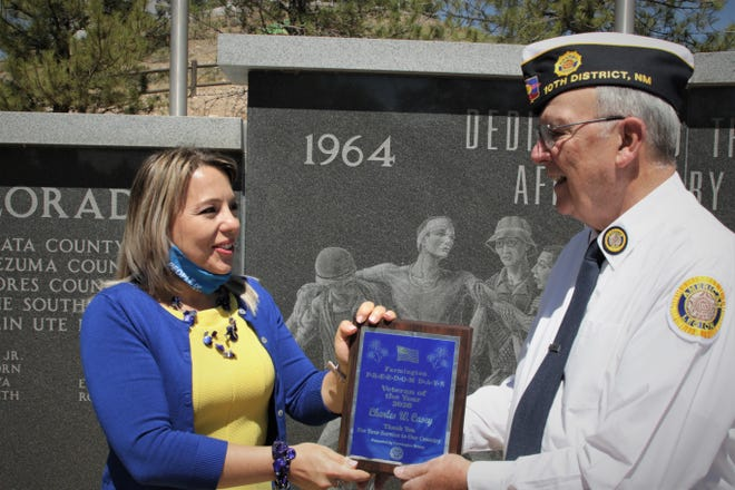 Olena Erickson, president of the Farmington Rotary Club, and Charlie Casey hold Casey's Farmington Freedom Days Veteran of the Year plaque on Aug. 7, 2020, during a presentation ceremony at Vietnam Veterans Park in Farmington.