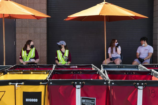 Arizona State University Community Assistants and A+ Movers employees wait for residents to arrive to move into Arizona State University Downtown Phoenix Campus residence hall Taylor Place in Phoenix on Aug. 7, 2020.