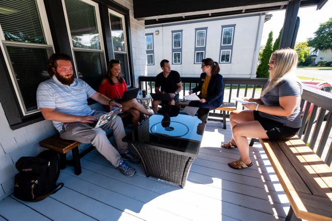 From left, Grant Moore, Carol Hall, Jim Beiwer, Jessie Wiegand and Tatum Brooks socialize while working on the front porch of The Hatch Thursday, Aug. 6, 2020, in Port Huron. Matt Brooks, who also owns The Roost and the former Loft 912, is opening the new co-working and meeting space.