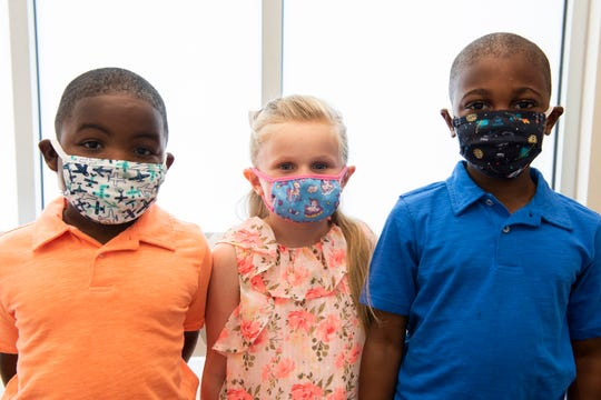 Caleb, 4, Elizabeth, 5, and Callen McNemar, 7, show the proper way for children to wear a mask.