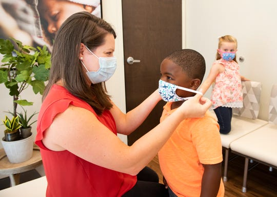 Sarah McNemar, Medical Director of Parkside Pediatrics' Powdersville office, shows her son Caleb, 4, how to properly put on a mask.