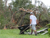 Workers, many of them volunteers, clear debris from a field at C-Line Stables in Townsend Friday after tropical storm Isaias brought a tornado that swept from Dover to Glasgow earlier this week.