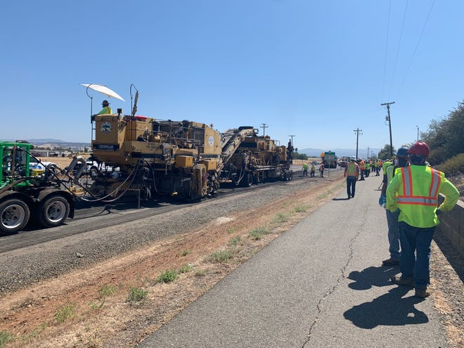 "The ""recycling train'' scoops up the old asphalt, grinds it, blends it with a binder and lays it down to form the new pavement."