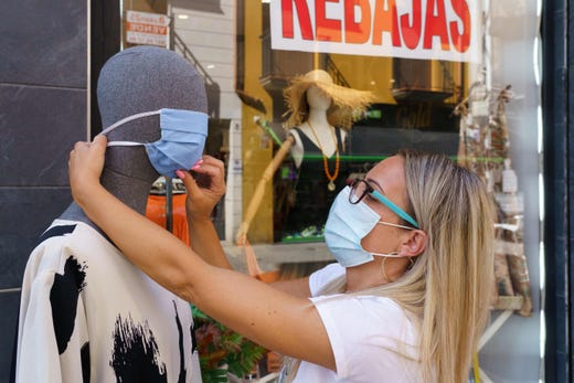 A woman places a mask on a mannequin outside a clothing store in Aranda de Duero, near Burgos, on August 7, 2020, on the first day of a two week lockdown in an attempt to limit the contagion of the new coronavirus COVID-19 in the area.