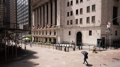 People pass the New York Stock Exchange, Thursday, July 30, 2020. Wall Street is stalling on Friday, Aug. 7 as a whirlwind of worries about rising U.S-China tensions and whether Congress can deliver more aid for the economy threaten to halt its big run.