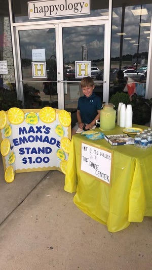 Max mans his lemonade stand in front of happyology in Thompson Square.