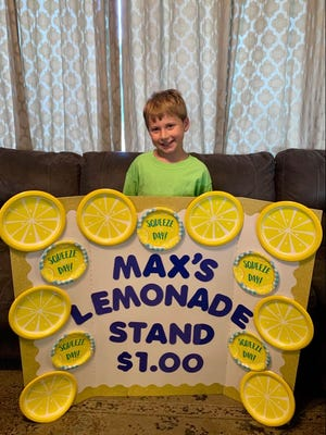 Eight-year-old Max Rickets shows off the sign from his lemonade stand. Last Saturday, he earned $610 selling lemonade, and donated half of his proceeds to The Grace Center of Southern Oklahoma. Once additional donations were added to the total, he raised $2,000 for the organization.