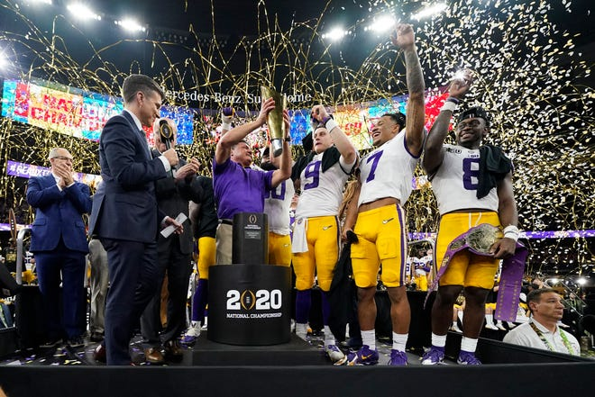 FILE - In this Jan. 13, 2020, file photo, LSU head coach Ed Orgeron holds the trophy after the team's victory over Clemson in an NCAA College Football Playoff national championship game in New Orleans.