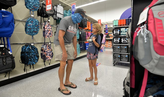 Rosie Trauthwein, 7, tries on a new backpack while shopping with her dad, Donny Trauthwein, at Academy Sports + Outdoors in Jacksonville on Saturday during the statewide Back-to-School Sales Tax Holiday, which continues through Sunday. [Dede Smith/For the Times-Union]