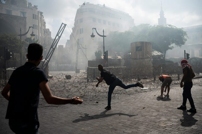 People clash with police during a protest Saturday against the political elites and the government after last week's deadly explosion at Beirut port which devastated large parts of the capital and killed more than 150 people, in Beirut, Lebanon. [Felipe Dana/The Associated Press]