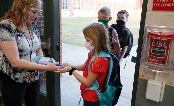 Wearing masks to prevent the spread of COVID19, elementary school students use hand sanitizer Wendesday before entering school for classes in Godley, Texas. As schools reopen around the country, their ability to quickly identify and contain coronavirus outbreaks before they get out of hand is about to be put to the test. [LM Otero/The Associated Press]