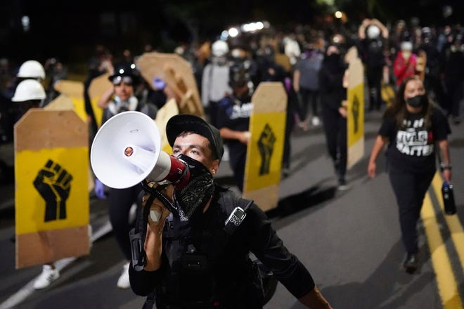 A protester leads a crowd of demonstrators toward the Multnomah County Sheriff's Office on Friday in Portland, Ore. [Nathan Howard/The Associated Press]