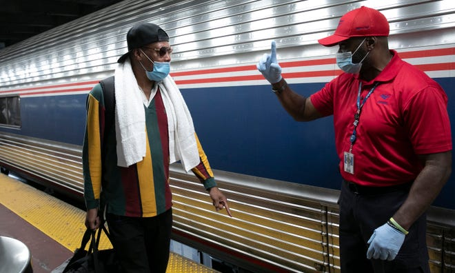 A traveler arriving on a train that originated in Miami gets directions from a porter, right, at Amtrak's Penn Station in New York City on Friday. Mayor Bill de Blasio is asking travelers from 34 states, including Florida where COVID-19 infection rates are high, to quarantine for 14 days after arriving in the city. [MARK LENNIHAN/THE ASSOCIATED PRESS]