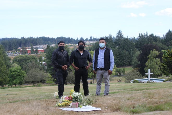 The Matias Mendoza family at the grave site of patriarch Mariano Matias Mendoza, who died from COVID-19 in July.  His younger brothers Juan (left) and Prudencio (center), and his son Carlos (right), remember Mariano as a leader in the Guatemalan community.