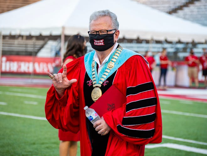 University President Dr. Joseph Savoie waves the UL hand sign as he enters the stadium for the 2020 graduation ceremony at Cajun Field Friday, August 7, 2020.