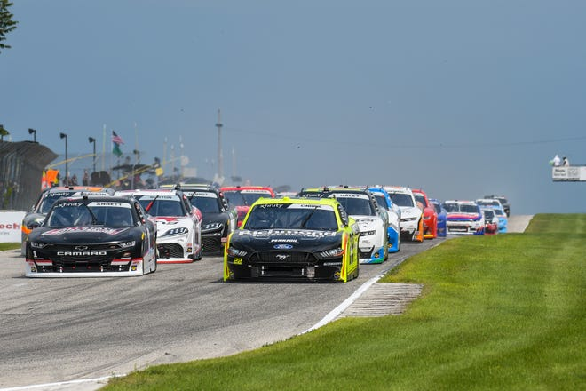 Michael Annett, left, and Austin Cindric lead the field into Turn 1 at the start of the 2020 Henry 180 NASCAR Xfinity Series race at Road America.