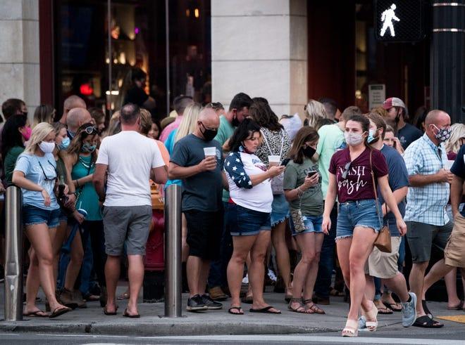 Pedestrians wear masks on Lower Broadway in Nashville, Tenn., Friday, Aug. 7, 2020.