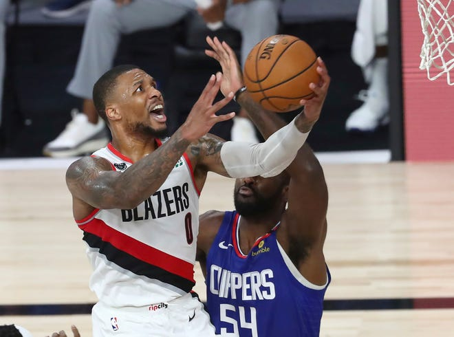 Portland Trail Blazers guard Damian Lillard (0) shoots past Los Angeles Clippers' Patrick Patterson (54) during the second half in an NBA basketball game Saturday, Aug. 8, 2020, in Lake Buena Vista, Fla.