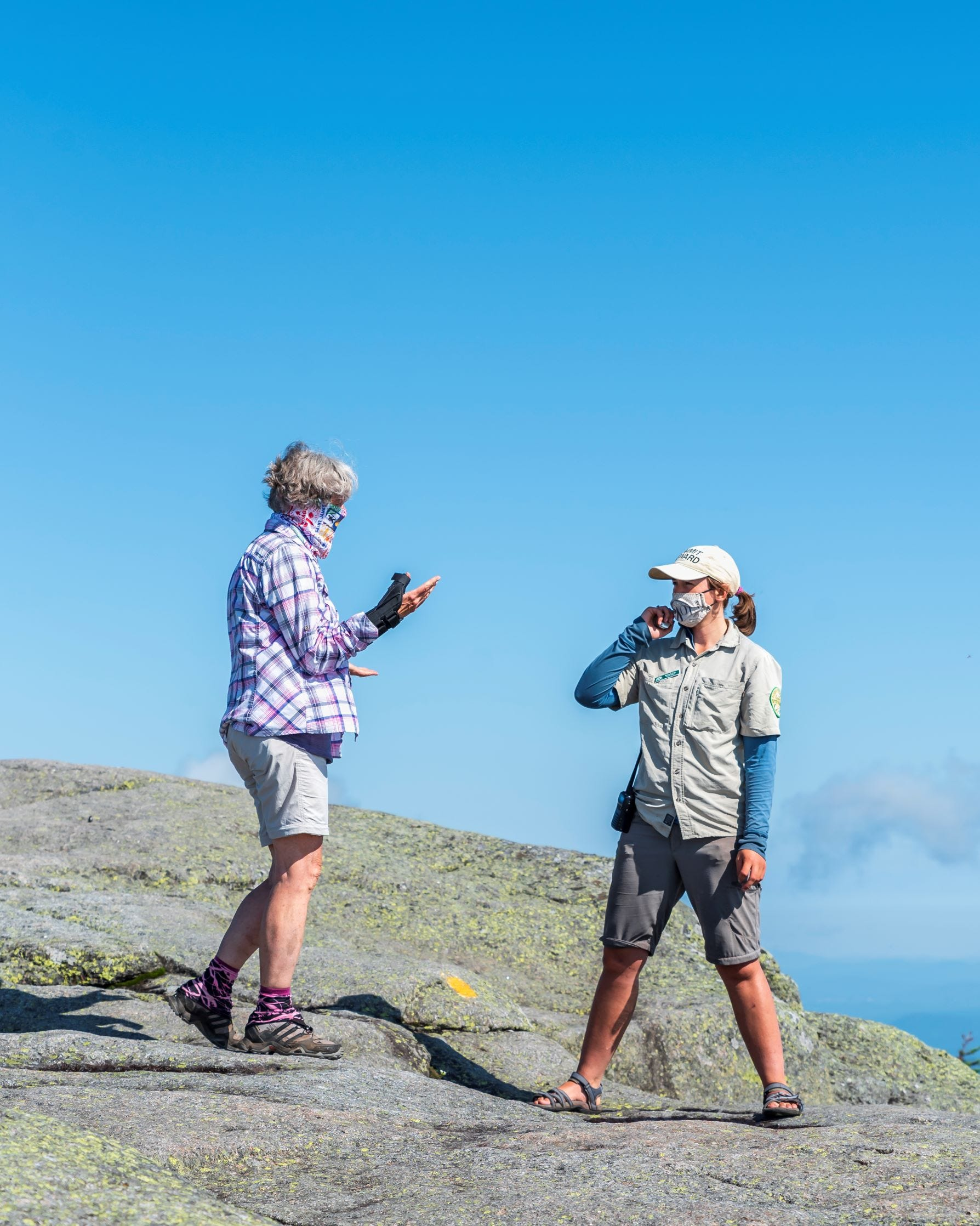 Michaela Dunn, a steward with the Summit Steward Program in the High Peaks of the Adirondack Park, talks with a hiker earlier this summer.