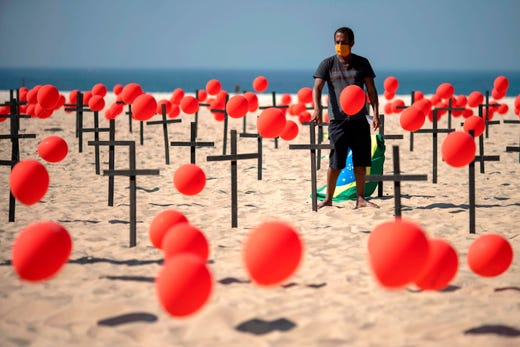 A demonstrator with a Brazilian flag is seen beside crosses before a thousand red balloons are released, during a tribute to COVID-19 victims organized by the Rio de Paz NGO at the Copacabana beach in Rio de Janeiro, Brazil, on August 08, 2020.