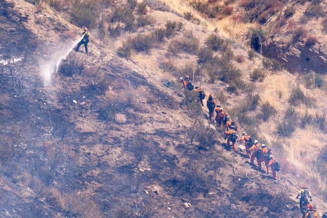 Hand crews work on hot spots in rugged terrain along Bouquet Canyon road in Saugus, Calif., late last week. A brush fire in Saugus is threatening structures and prompting evacuations on Thursday, the U.S. Forest Service said. [David Crane/The Associated Press]