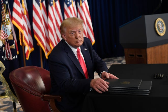 President Donald Trump prepares to sign four executive orders during a news conference at the Trump National Golf Club in Bedminster, N.J., on Saturday. [Susan Walsh/The Associated Press]