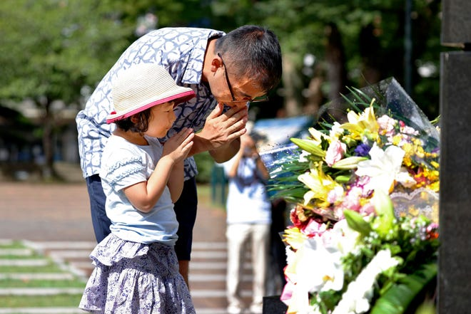 A man and his daughter pray for the victims of U.S. atomic bombing at the Atomic Bomb Hypocenter Park in Nagasaki, southern Japan, on Sunday. Nagasaki marked the 75th anniversary of the atomic bombing on Sunday. [Takuto Kaneko/The Associated Press]
