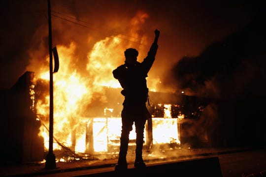 A check-cashing company building burns in Minneapolis during May unrest.