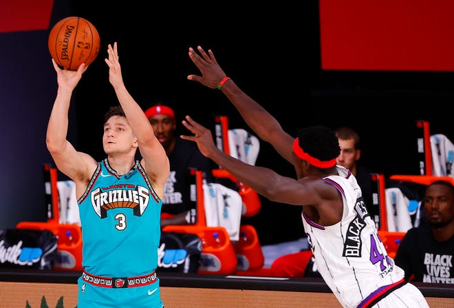 Grayson Allen, left, of the Memphis Grizzlies' attempts a three-point basket against Pascal Siakam, right, of the Toronto Raptors during the first half of an NBA basketball game Sunday, Aug. 9, 2020, in Lake Buena Vista, Fla. (Kevin C. Cox/Pool Photo via AP)