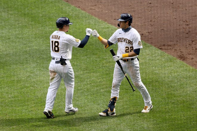Keston Hiura is greeted by Christian Yelich after belting a solo home run in the seventh inning against the Reds. Yelich would follow with a solo blast to center of his own.