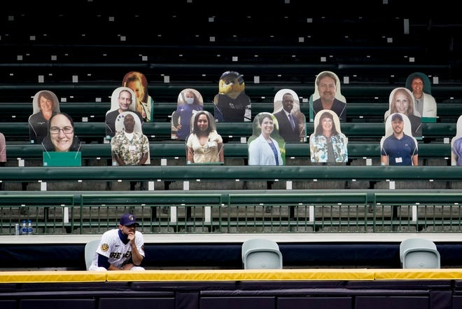 Brewers relief pitcher Justin Grimm watches from the makeshift bullpen in front of cardboard fan cutouts.