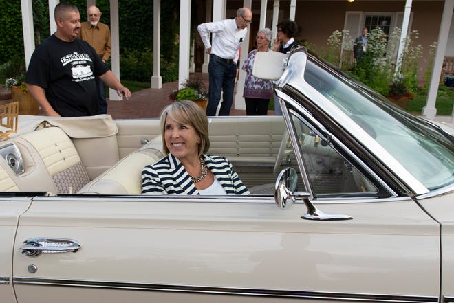 Governor Michelle Lujan Grisham sitting in Fred Rael's award-winning lowrider at the Governor's Mansion last July. The governor was hosting a gathering of secretaries of state from across the nation.