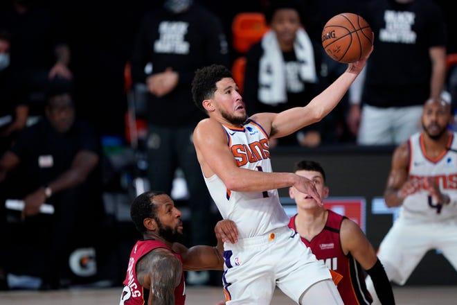 Phoenix Suns' Devin Booker (1) goes to the basket over Miami Heat's Andre Iguodala, left, and Tyler Herro, right, during the second half of an NBA basketball game, Saturday, Aug. 8, 2020, in Lake Buena Vista, Fla. The suns won 119-112. (AP Photo/Ashley Landis, Pool).