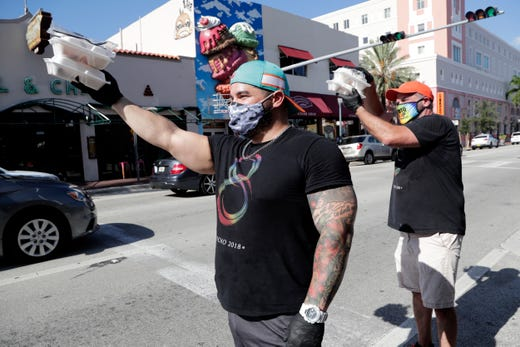 Jonathan Lasanas, left, and Damian Pardo, right, pass out free meals during an event sponsored by the Gay8 Festival during the coronavirus pandemic, Aug. 7, 2020, in the Little Havana neighborhood in Miami. The Gay8 Festival is an annual Hispanic LGBTQ celebration in Little Havana.