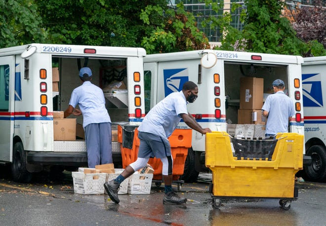 Letter carriers load mail trucks for deliveries at a U.S. Postal Service facility in McLean, Virginia, on July 31, 2020.