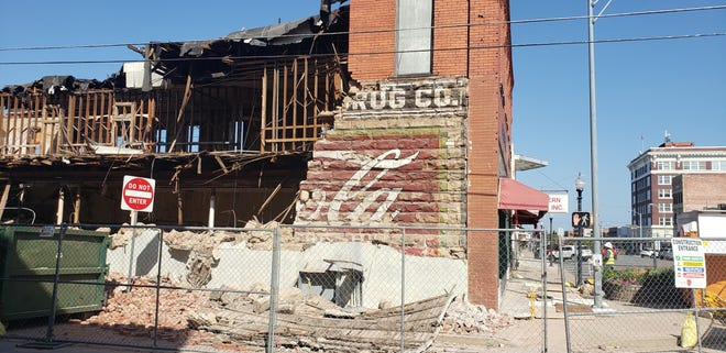 An old advertisement previously behind a stucco wall is now visible at the former Jim Tees building on Main Street.