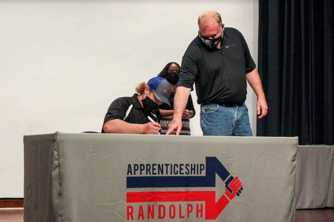 Maintenance apprentice Aiden Register signs as his mentor, Maintenance Manager Al Fogleman of Technimark, watches.